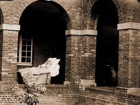 Santa Teresita en la cama, bajo los arcos del Claustro del Carmelo de Lisieux, aproximadamente un mes antes de fallecer