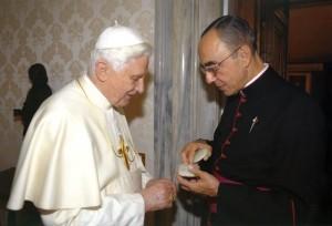 Mons. João S. Clá Dias EP hace la entrega de un Rosario de rubi con oro al Santo Padre.